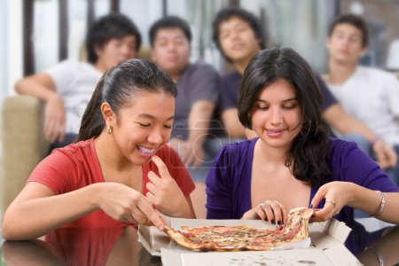 Photo for The girls got the first chance to eat pizza, while the boys looking at them jealously - Royalty Free Image