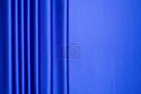 Photo pour Le satin bleu est disposés en bandes avec plus de la moitié pour l'espace de la copie, peut être utilisé pour le fond, conception de cartes, etc.. - image libre de droit
