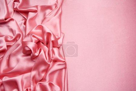 Photo pour Le satin rose est disposés en complexe avec plus de la moitié pour l'espace de la copie, peut être utilisé pour le fond, conception de cartes, etc.. - image libre de droit