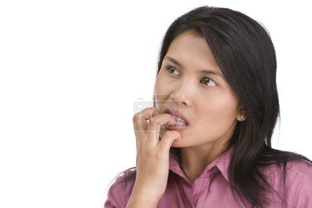 Nervous and biting her fingernail
