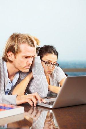 Photo pour Couple déprimé ont l'air si désespéré devant l'ordinateur portable - image libre de droit
