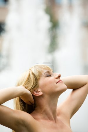 Photo for Image of relaxed woman touching her hair with closed eyes and glad expression on her face - Royalty Free Image