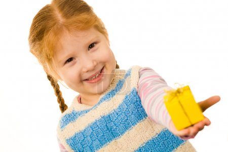 Photo for Little redheaded girl giving somebody small present in yellow box and smiling - Royalty Free Image