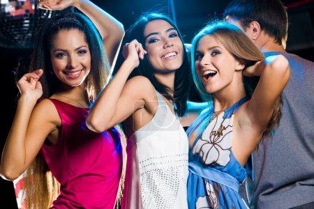 Photo pour Trois filles riantes dansant ensemble dans la clib à la fête avec l'homme en arrière-plan - image libre de droit