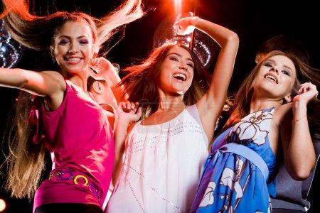 Photo pour Trois danseurs intelligents se déplaçant à la discothèque tout en levant les bras - image libre de droit