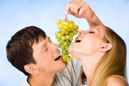 Photo pour Portrait d'attrayant voulant manger des raisins verts - image libre de droit