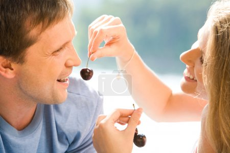 Photo for Portrait of pretty woman holding cherry with man near by - Royalty Free Image
