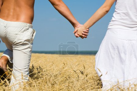 Photo for Close-up of woman and man holding by hands in the field - Royalty Free Image
