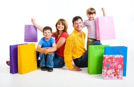 Photo for Image of happy parents and their two sons sitting in studio with shopping bags near by - Royalty Free Image