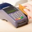 Close-up of human hand putting credit card into pa...