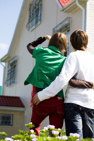 Photo for Rear view of embracing couple looking at new house outdoors - Royalty Free Image