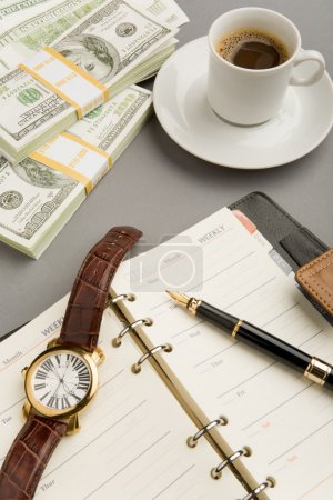 Photo for Image of open notepad with fountain pen and watch on it with cup of coffee and dollar banknotes near by - Royalty Free Image