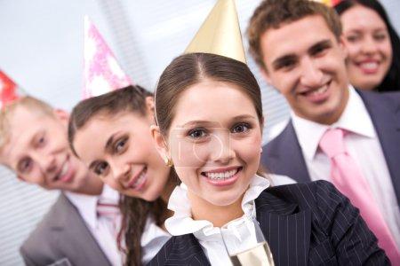 Foto de Retrato de mujer alegre con gorra de cumpleaños mirando a la cámara en el fondo de los colegas - Imagen libre de derechos