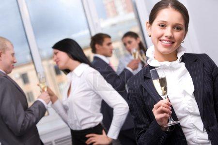Photo pour Portrait de jolie fille avec flûte à champagne regardant la caméra et souriant - image libre de droit