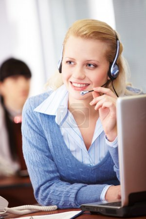 Photo for Pretty operator speaking on headphone in the office - Royalty Free Image