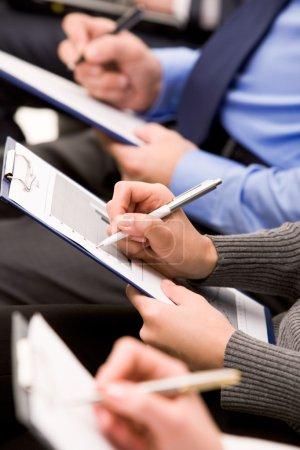 Foto de Primer plano de las manos humanas con plumas sobre documentos comerciales - Imagen libre de derechos