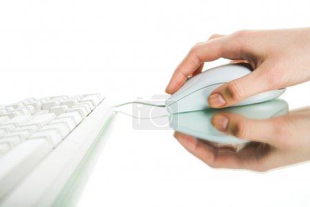 Photo pour Prise de vue de la main humaine touchant la souris et cliquant sur son bouton avec clavier à proximité - image libre de droit