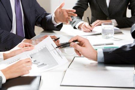 Photo pour Gros plan de l'homme d'affaires, expliquer un plan financier à mes collègues à la réunion - image libre de droit
