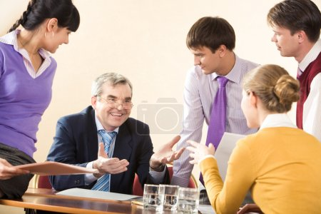 Photo for Group of successful managers communicating with senior boss at meeting - Royalty Free Image