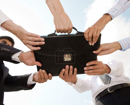 Photo for Photo of human hands touching a black briefcase - Royalty Free Image