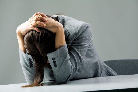 Photo pour Photo d'une femme déprimée assise au travail et en deuil - image libre de droit