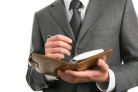 Photo pour Gros plan de l'homme d'affaires détenant le bloc-notes prêt à écrire quelque chose vers le bas - image libre de droit