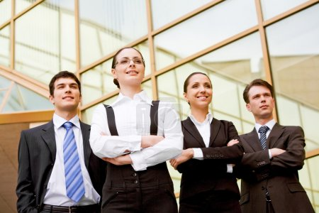 Photo for Portrait of smart associates standing in row and looking forwards with successful woman in front - Royalty Free Image