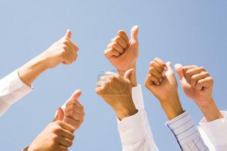 Foto de Imagen de varias manos humanas mostrando los pulgares para arriba contra el claro cielo azul - Imagen libre de derechos