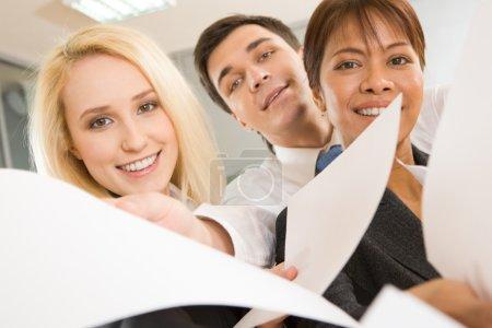 Photo pour Vue de face de collègues heureux regardant la caméra avec des sourires et donnant des documents - image libre de droit