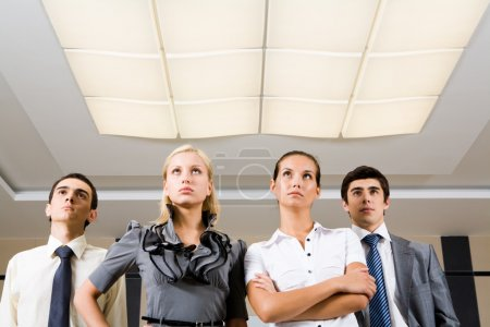 Photo for Several confident employees standing in row and looking upwards seriously - Royalty Free Image