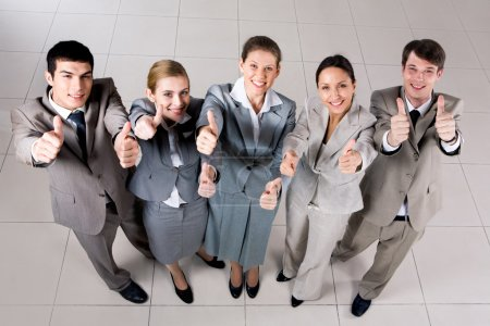 Photo for Above view of several successful partners looking at camera and showing thumbs up - Royalty Free Image