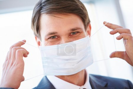 Photo for Portrait of businessman holding protective mask before himself - Royalty Free Image