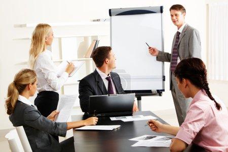 Photo pour Image de l'entreprise à puce en regardant leur chef pendant qu'il expliquer quelque chose sur le tableau blanc au cours du séminaire - image libre de droit