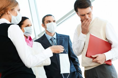 Photo for Group of associates in protective masks giving one to sick man - Royalty Free Image