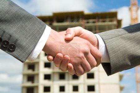 Photo pour Photo de poignée de main des partenaires commerciaux après avoir conclu un accord sur le fond du bâtiment en construction - image libre de droit