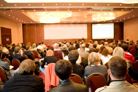 Photo for Rear view of many listeners sitting on chairs during lecture at conference - Royalty Free Image