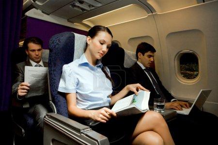 Photo pour Image d'une jolie fille lisant un magazine alors qu'un bel homme tapant à côté d'elle dans un avion - image libre de droit