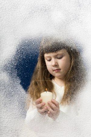 Photo pour Image d'une jeune fille avec une bougie dans les mains la regardant derrière la fenêtre - image libre de droit
