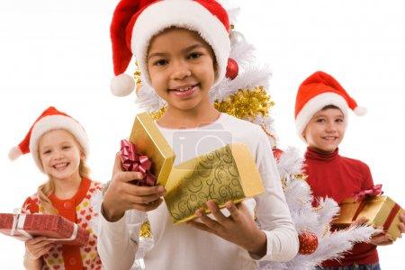 Photo pour Fille heureuse avec boîte cadeau regardant la caméra avec ses amis en arrière-plan - image libre de droit