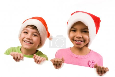 Photo for Photo of happy friends in Santa caps smiling at camera - Royalty Free Image