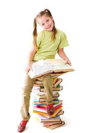 Photo pour Portrait d'écolière mignonne assise sur le dessus du tas avec livre ouvert et regardant la caméra - image libre de droit