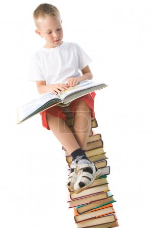 Photo for Image of schoolboy sitting on the heap of books and reading one of them - Royalty Free Image