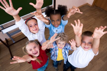 Photo for Image of cute schoolchildren looking at camera and laughing with their arms raised - Royalty Free Image