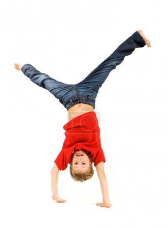 Photo for Playful lad standing on his arms with legs pointing upwards over white background - Royalty Free Image
