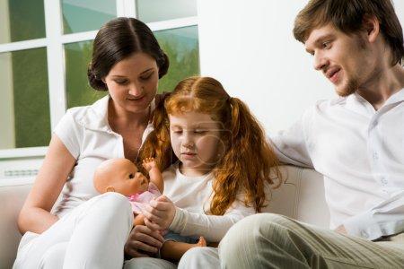 Photo pour Portrait de parents affectueux et de leur fille assis sur le canapé à la maison - image libre de droit
