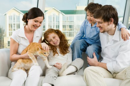 Photo for Portrait of young man and woman enjoying weekend day with their children and cute cat - Royalty Free Image