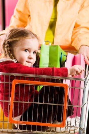 Photo pour Image de jolie fille assis dans une charrette à bras pendant que ses parents faire du shopping - image libre de droit