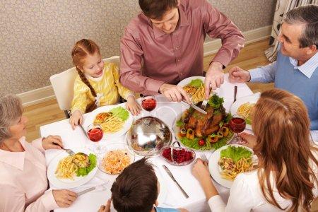 Photo pour Image de la grande famille assis à la table de fête et de manger la salade et le rôti de dinde - image libre de droit