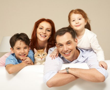 Photo for Portrait of siblings and their parents with cute cat looking at camera - Royalty Free Image
