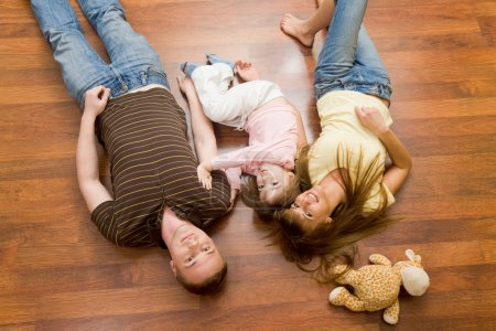Photo for View from above of resting family lying on the floor and looking at camera - Royalty Free Image